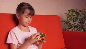 Un niño que juega con un cubo del ` s de Rubik almacen de metraje de vídeo