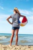 Un niño que juega con una bola en la playa Imagen de archivo