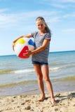 Un niño que juega con una bola en la playa Imagen de archivo libre de regalías