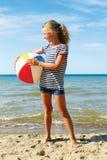 Un niño que juega con una bola en la playa Fotografía de archivo libre de regalías