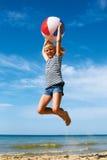 Un niño que juega con una bola en la playa Imágenes de archivo libres de regalías