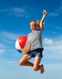 Un niño que juega con una bola en la playa Foto de archivo