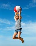 Un niño que juega con una bola en la playa Imagenes de archivo