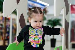 Un niño que juega en un centro comercial en un patio en el fondo de las ventanas de la tienda Imágenes de archivo libres de regalías