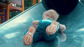 Un niño que juega en una diapositiva de los niños almacen de metraje de vídeo