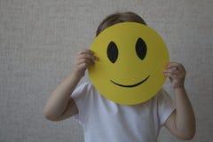 Un niño que lleva a cabo un círculo amarillo con el emoticon de la cara de la sonrisa en vez de la cabeza Foto de archivo libre de regalías