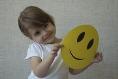 Un niño que lleva a cabo un círculo amarillo con el emoticon de la cara de la sonrisa en vez de la cabeza Fotografía de archivo libre de regalías