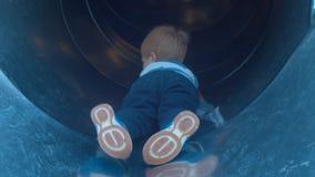 Un niño que miente en el vientre en la diapositiva de los niños metrajes