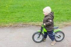 Un niño que monta una bici sin el pedal Un niño pequeño aprende a fotografía de archivo