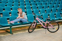 Un niño que presenta con la bici niño de la muchacha que se relaja en el estadio Foto de archivo libre de regalías