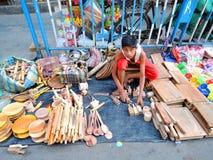 Un niño que vende los artículos de la cocina hechos de la madera Imagen de archivo