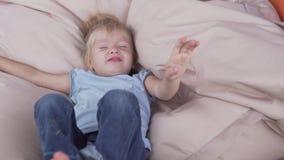 Un niño ríe y miente en una almohada grande en el mirador en el verano en una granja almacen de video