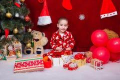 Un niño satisfecho recibió los regalos de la Navidad Imágenes de archivo libres de regalías