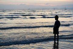Un niño se coloca en el mar de la puesta del sol en Krabi, Tailandia imagenes de archivo