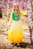 Un niño se coloca entre el ledum y el abedul en vestido amarillo verde y la sonrisa Imágenes de archivo libres de regalías
