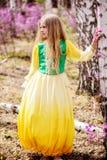 Un niño se coloca entre el ledum y el abedul en vestido amarillo verde y la sonrisa Imagenes de archivo