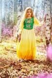 Un niño se coloca entre el ledum y el abedul en vestido amarillo verde y la sonrisa Fotografía de archivo libre de regalías