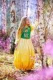 Un niño se coloca entre el ledum y el abedul en vestido amarillo verde y la sonrisa Foto de archivo