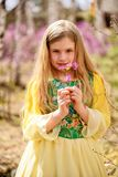 Un niño se coloca entre el ledum y el abedul en vestido amarillo verde y la sonrisa Foto de archivo libre de regalías