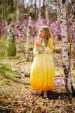 Un niño se coloca entre el ledum y el abedul en vestido amarillo verde y la sonrisa Fotos de archivo libres de regalías