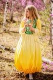 Un niño se coloca entre el ledum y el abedul en vestido amarillo verde y la sonrisa Fotografía de archivo
