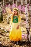 Un niño se coloca entre el ledum y el abedul en vestido amarillo verde, la sonrisa y el pelo de la mosca Fotos de archivo libres de regalías