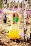 Un niño se coloca entre el ledum y el abedul en vestido amarillo verde, la sonrisa y el pelo de la mosca Imagen de archivo