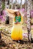 Un niño se coloca entre el ledum y el abedul en vestido amarillo verde, la sonrisa y el pelo de la mosca Foto de archivo libre de regalías