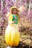 Un niño se coloca entre el ledum y el abedul en vestido amarillo verde, la sonrisa y el pelo de la mosca Imagenes de archivo