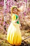 Un niño se coloca entre el ledum y el abedul en vestido amarillo verde, la sonrisa y el pelo de la mosca Imágenes de archivo libres de regalías