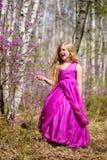 Un niño se coloca entre el ledum y el abedul en un vestido rosado y ríe Fotografía de archivo libre de regalías