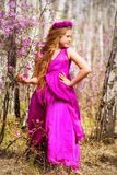Un niño se coloca entre el ledum y el abedul en un vestido y una sonrisa rosados Fotos de archivo
