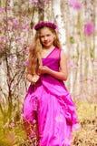Un niño se coloca entre el ledum y el abedul en un vestido y una sonrisa rosados Imagen de archivo