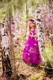 Un niño se coloca entre el ledum y el abedul en un vestido y una sonrisa rosados Imágenes de archivo libres de regalías