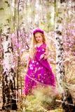Un niño se coloca entre el ledum y el abedul en un vestido y una sonrisa rosados Imagen de archivo libre de regalías