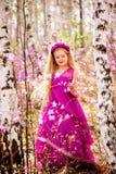 Un niño se coloca entre el ledum y el abedul en un vestido y una sonrisa rosados Fotos de archivo libres de regalías