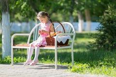 Un niño se sienta en un banco con una cesta de pan imágenes de archivo libres de regalías