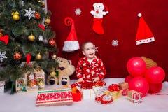 Un niño sonriente se sienta con muchos regalos de Navidad Foto de archivo