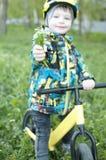 Un niño sostiene hacia fuera un ramo de flores, se sienta en una bicicleta Imágenes de archivo libres de regalías