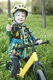 Un niño sostiene hacia fuera un ramo de flores, se sienta en una bicicleta Fotos de archivo