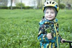 Un niño sostiene hacia fuera un ramo de flores, se sienta en una bicicleta Fotografía de archivo