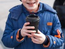 Un ni?o sostiene una taza de papel negra de bebida El adolescente se sostiene en la taza de las manos de caf? en el vidrio de pap foto de archivo