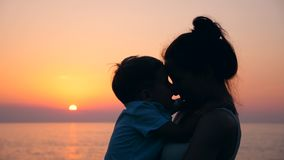 Un niño y su madre son de abrazo y que se besan en la puesta del sol Madre y bebé, concepto de la maternidad metrajes