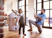 Un ni?o peque?o y un padre con las espadas del cart?n que juegan dentro en casa imágenes de archivo libres de regalías