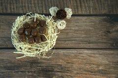 Un nid de paille avec des chocolats et et les boules décoratives sur une table en bois image libre de droits