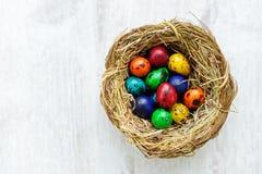 Un nido con le uova di Pasqua colorate a casa sul giorno di Pasqua Immagine Stock