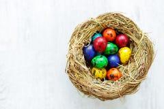 Un nido con le uova di Pasqua colorate a casa sul giorno di Pasqua Fotografia Stock