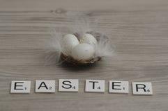 Un nido ha riempito di piccole uova bianche con la parola Pasqua Immagini Stock Libere da Diritti