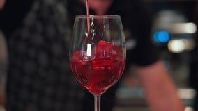 In un night-club o in un pub un barista che prepara un cocktail con ghiaccio e vino Il vino rosso sfocia nel vetro Lento-Mo video d archivio
