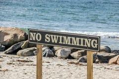 Un ` ninguna muestra del ` de la natación en una playa local Fotos de archivo libres de regalías
